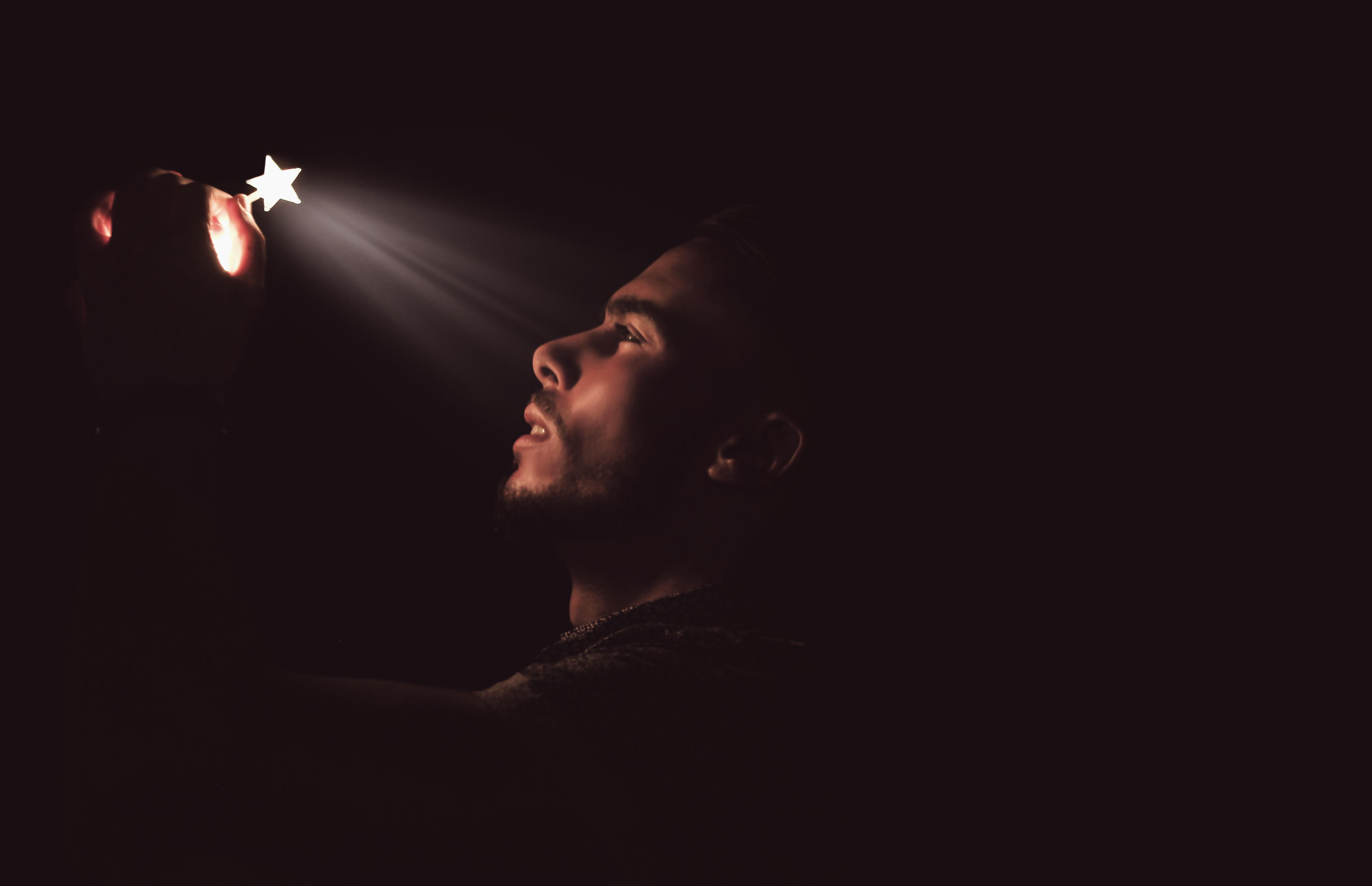 man holding white LED star