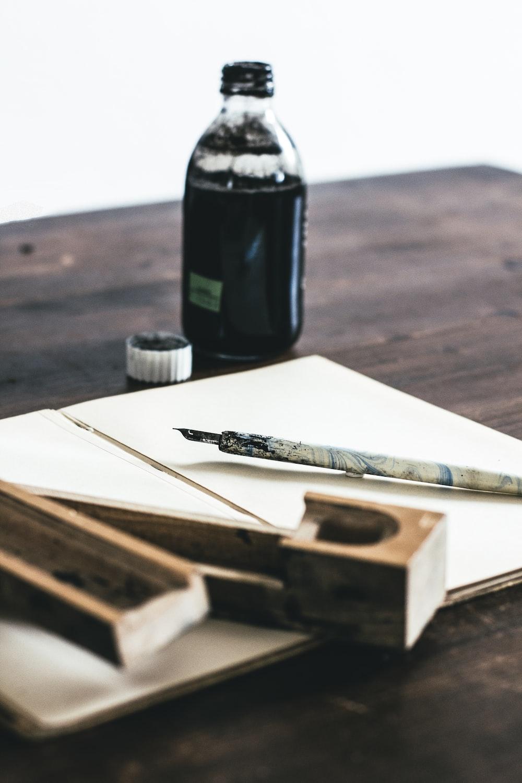 white quill pen near ink bottle