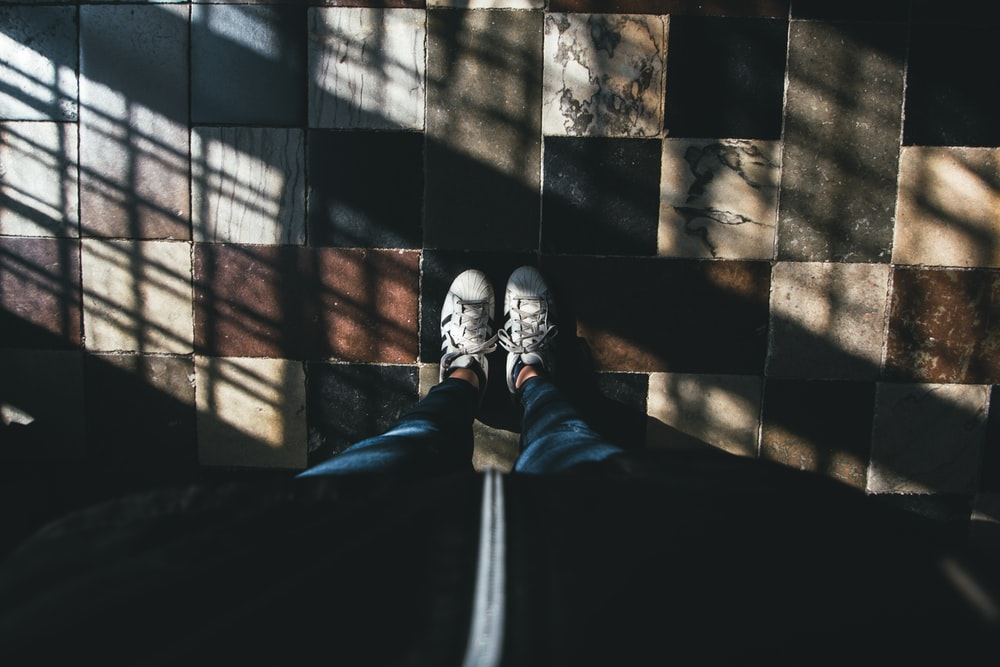 high-angle of person in blue pants and white sneakers standing on floor tiles
