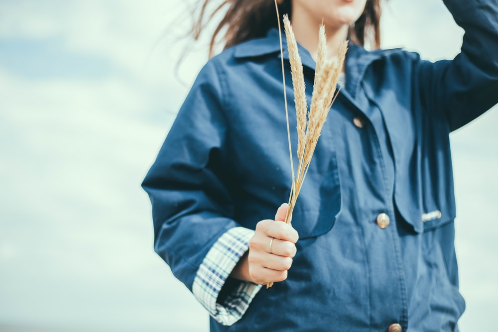 closeup photo of woman wearing blue top holding wheat