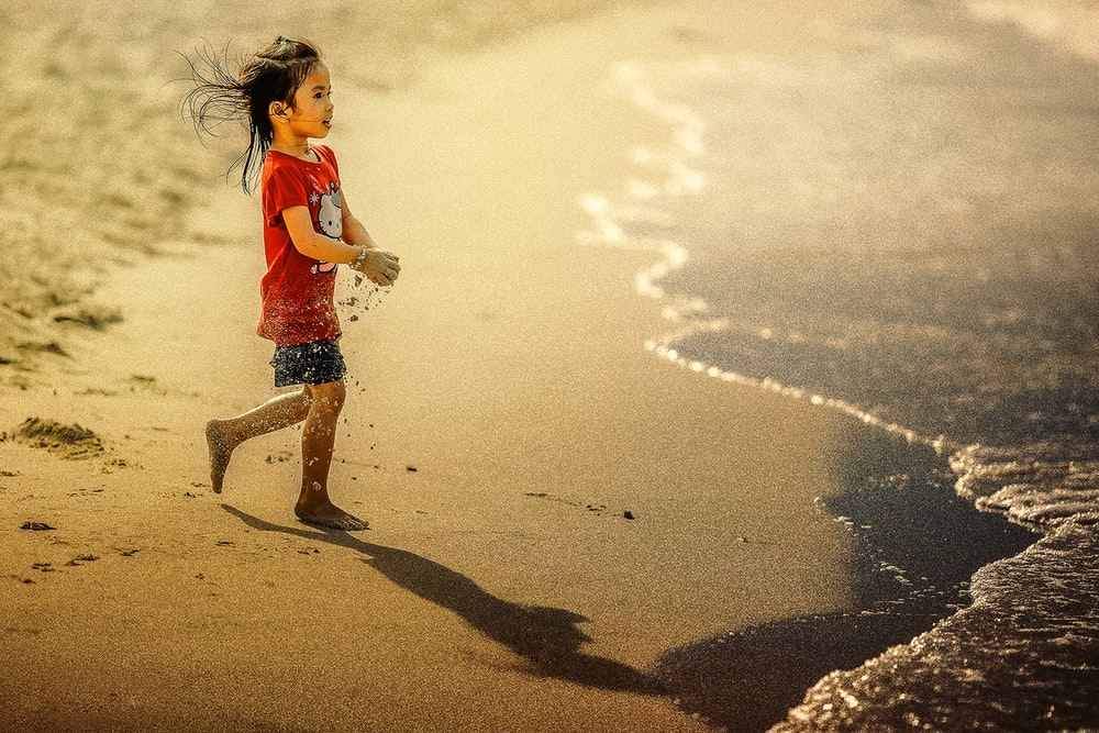 girl carrying sand on her hands while walking towards body of water