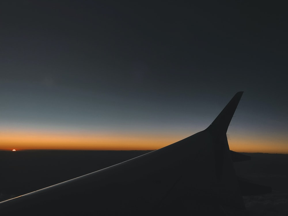 Silhouette of an airplane wing against a blue and yellow sunset