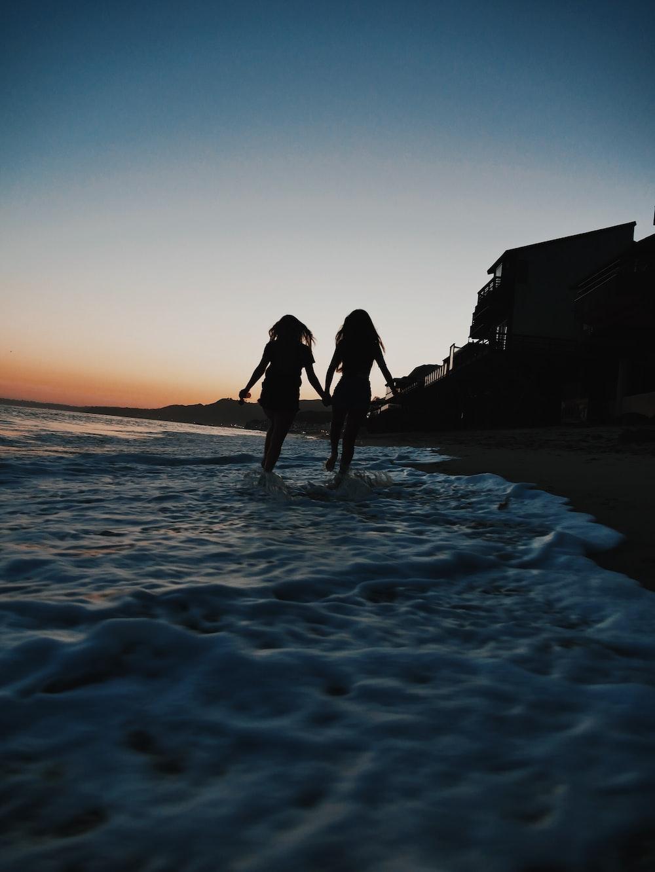 silhouette of two women running across seashore