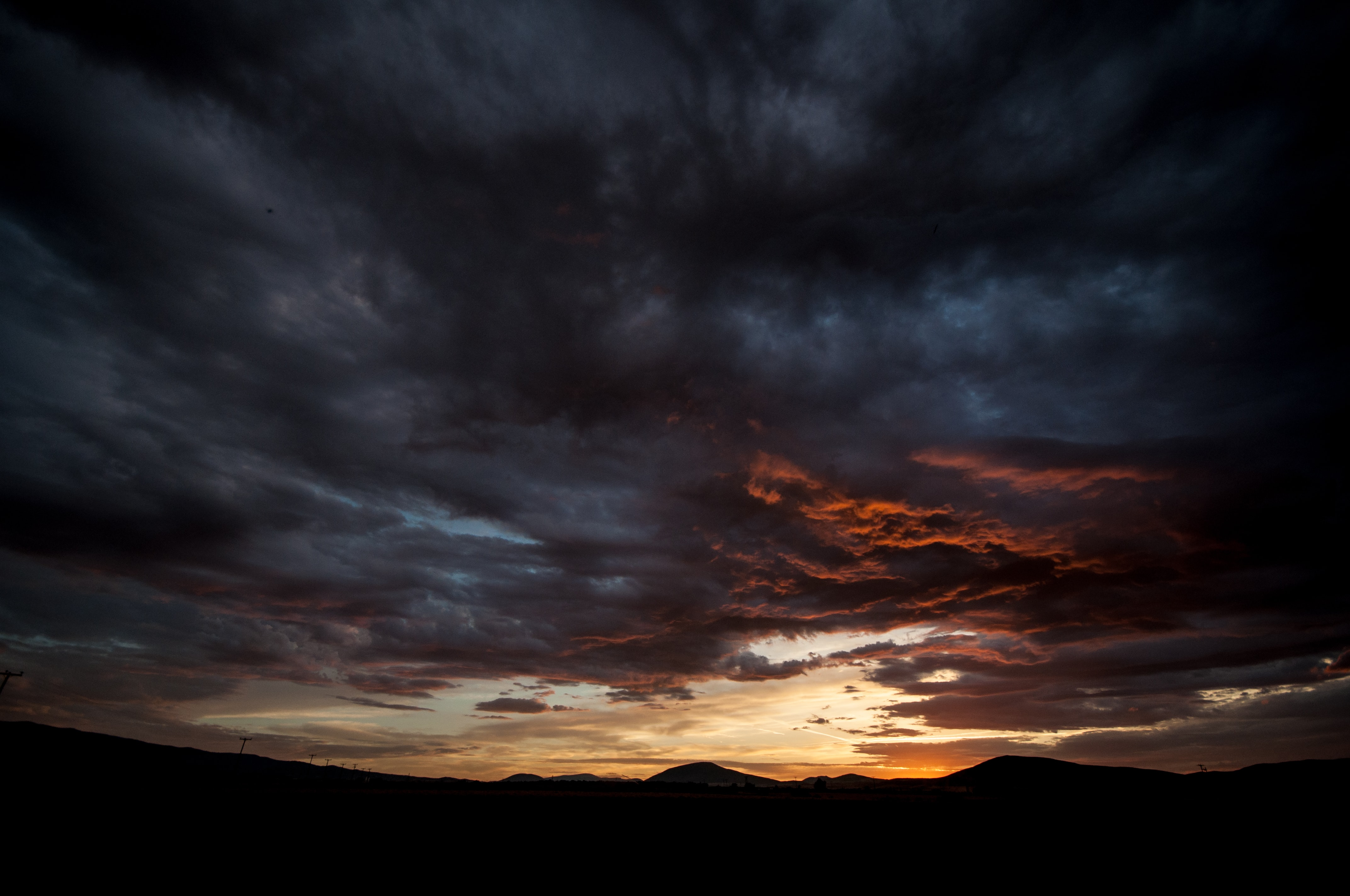 silhouette of mountains under cloudy sky