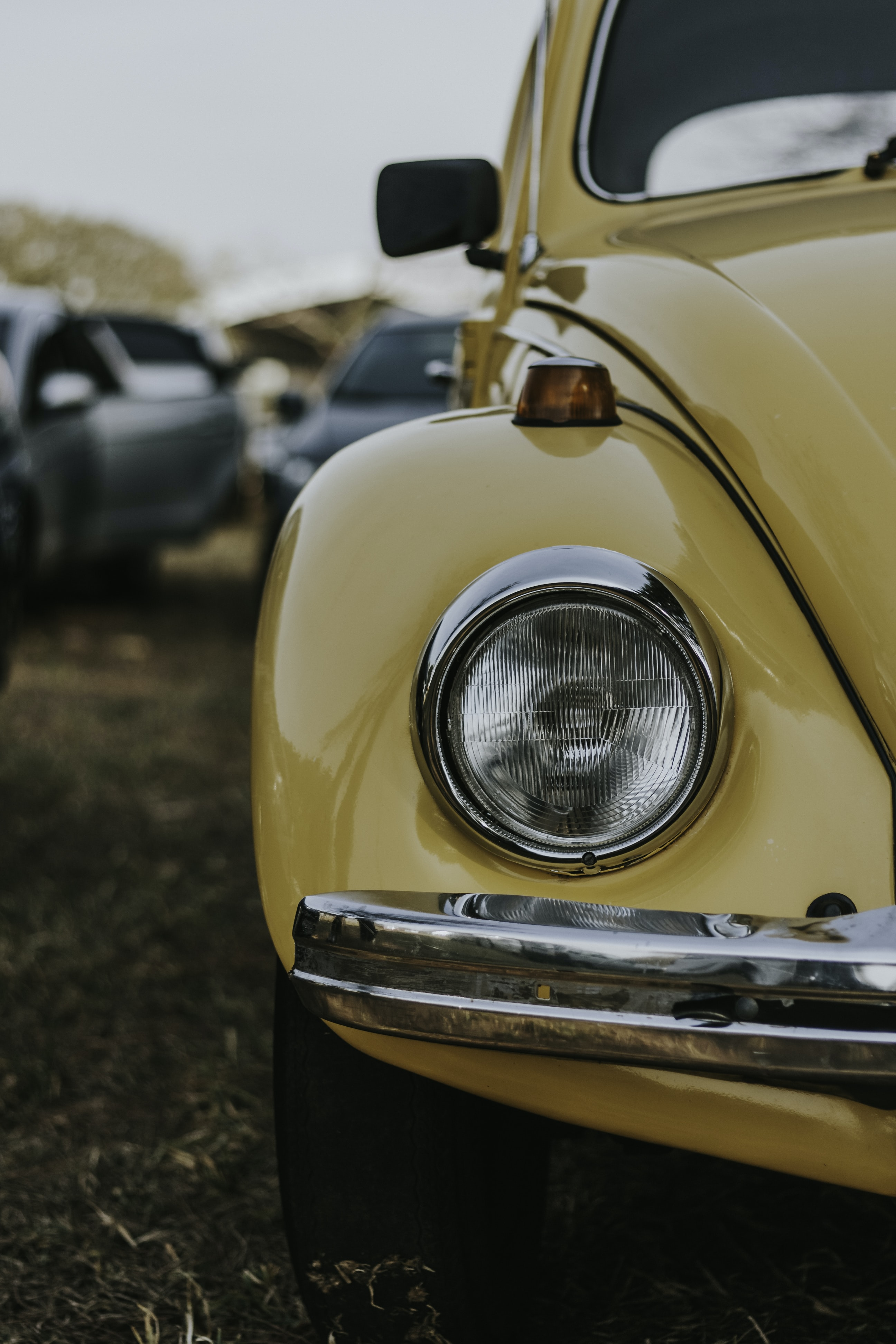 The passenger side headlight of a yellow car.
