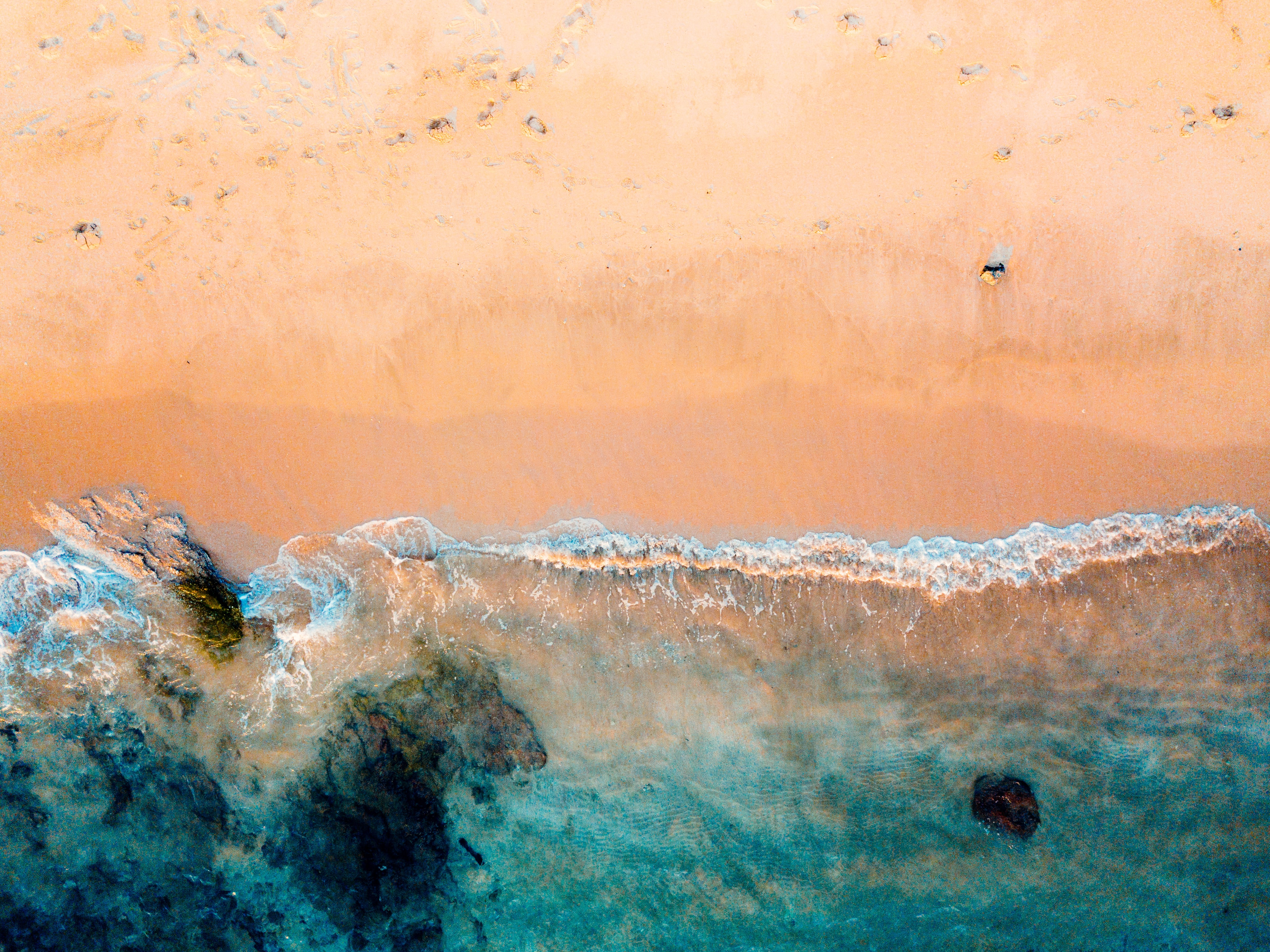 drone shot of beach and body of water on brown sand