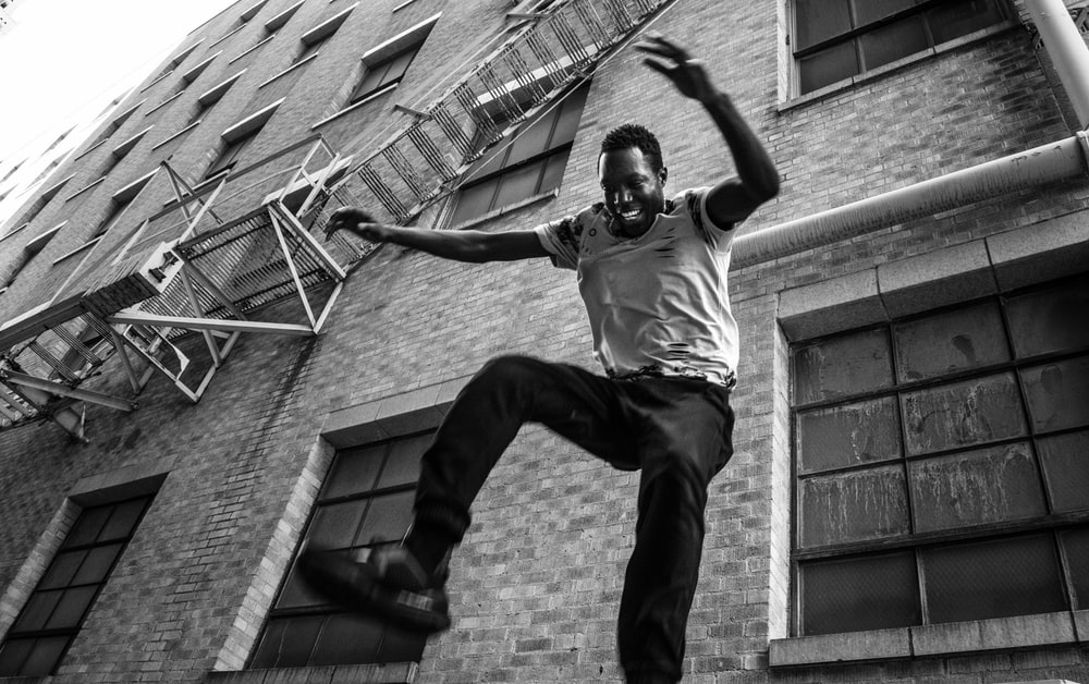 grayscale photography of man jumping near building