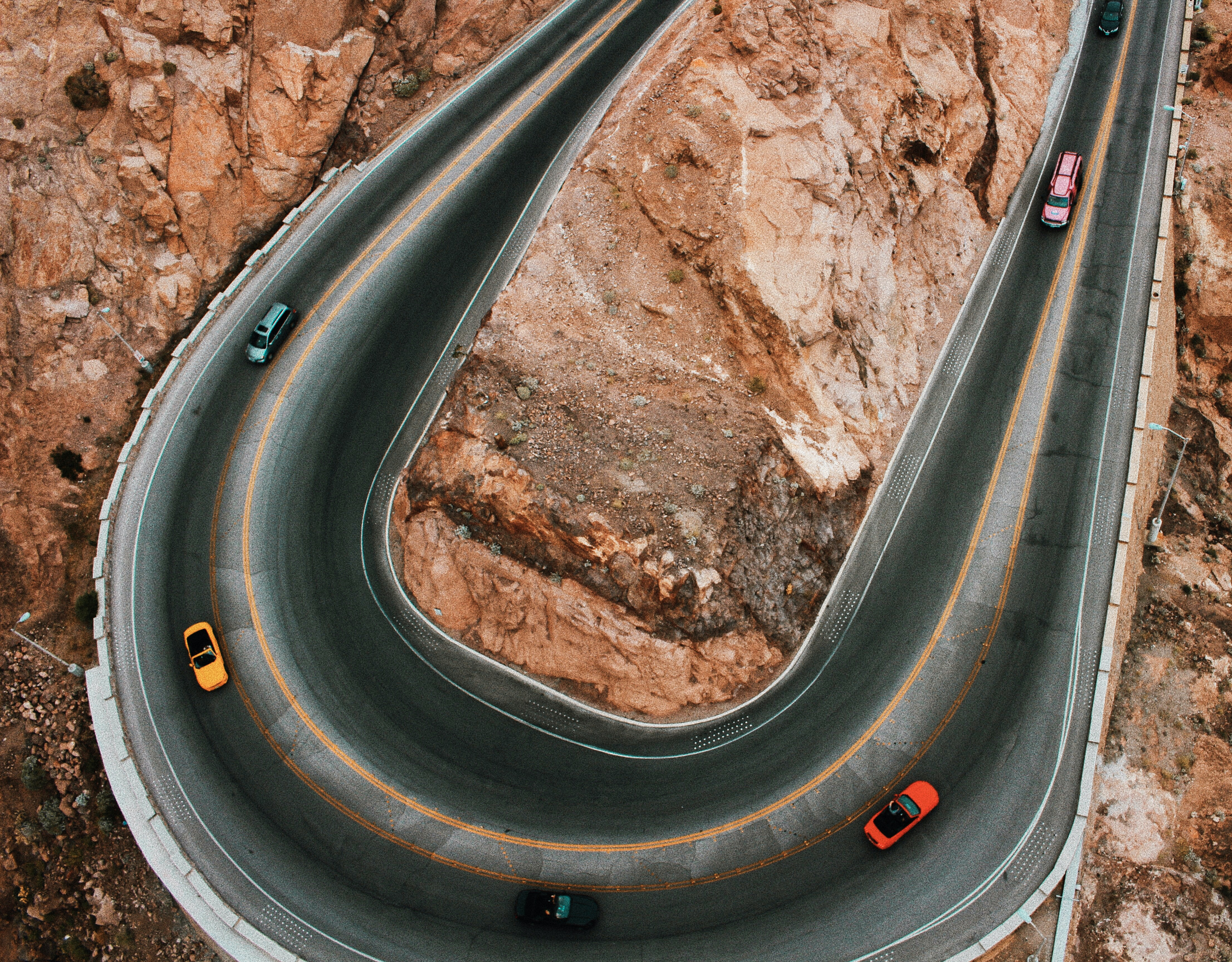 Colorful cars wind around a bend in the road through the mountains