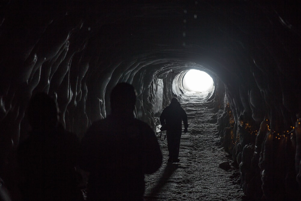 silhouette of three person walking inside tunnel