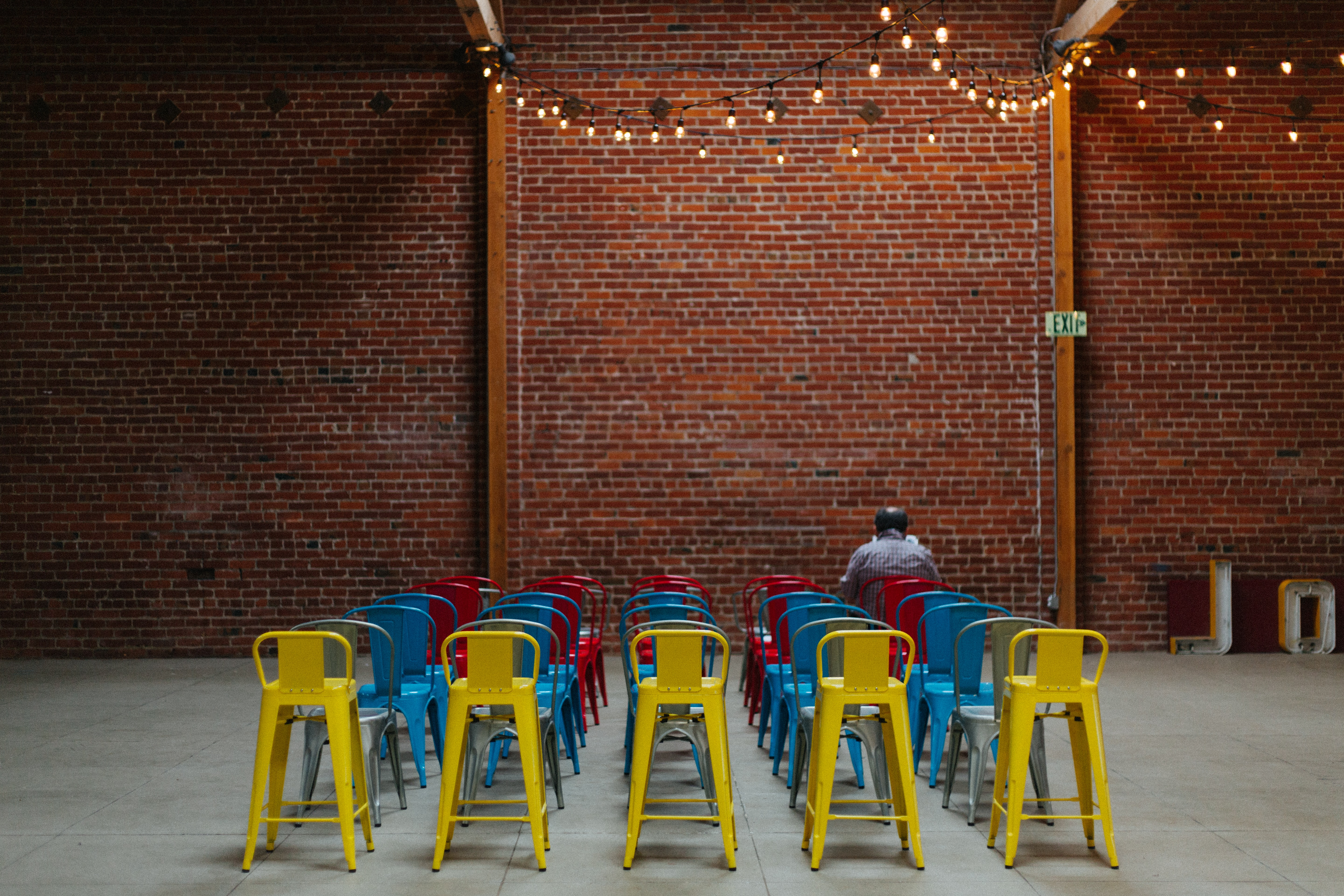 Person sits alone in rows of colorful chairs inside a decorated event space