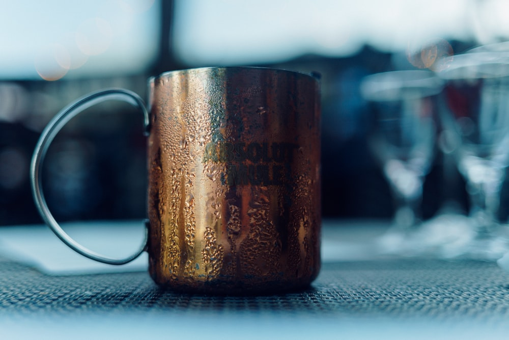 selective focus photo of copper-colored mug with water moist