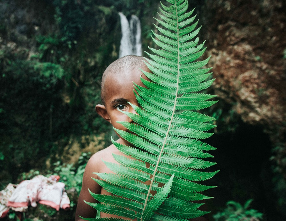boy standing in behind plant