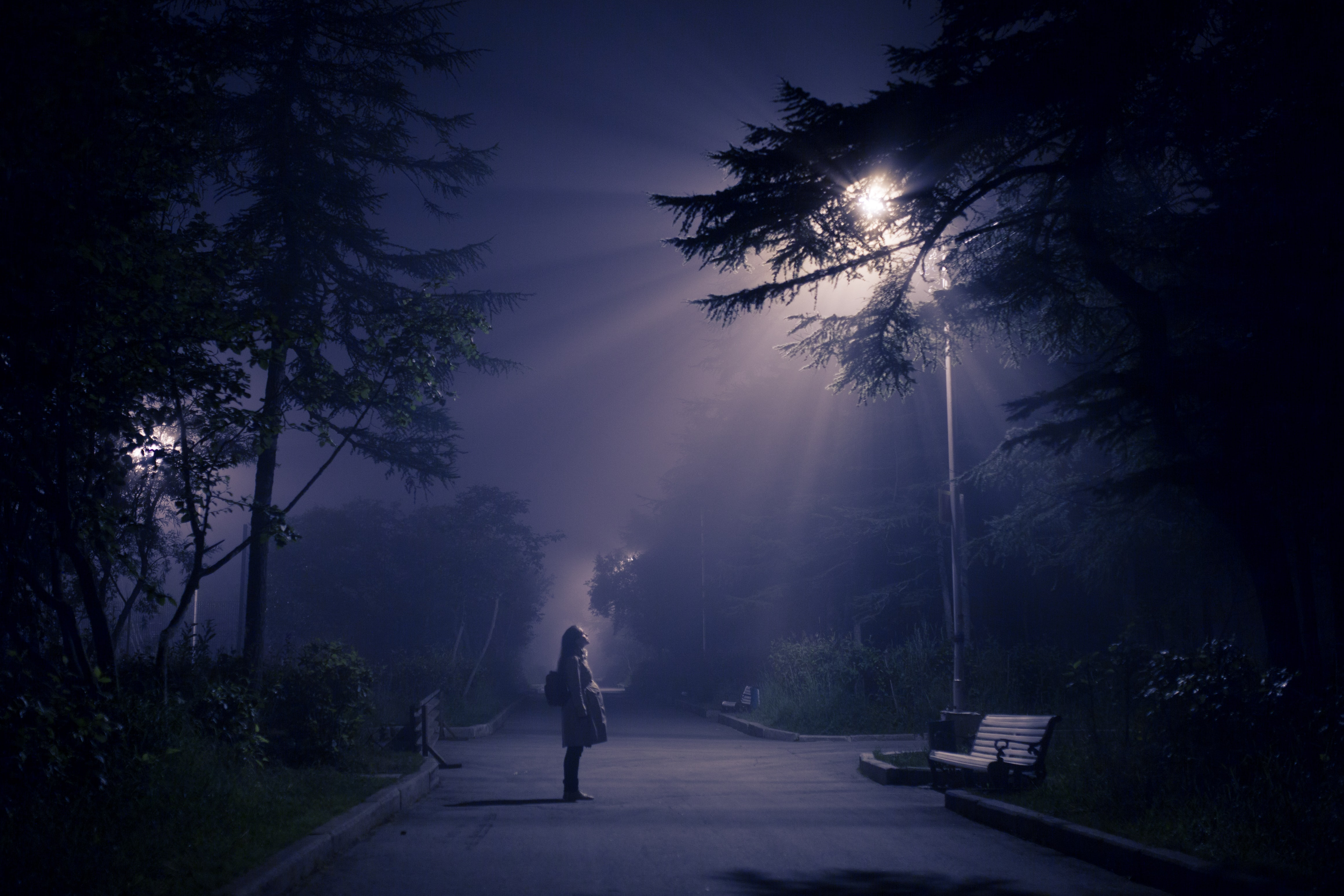 A person standing out after dark under a street light.