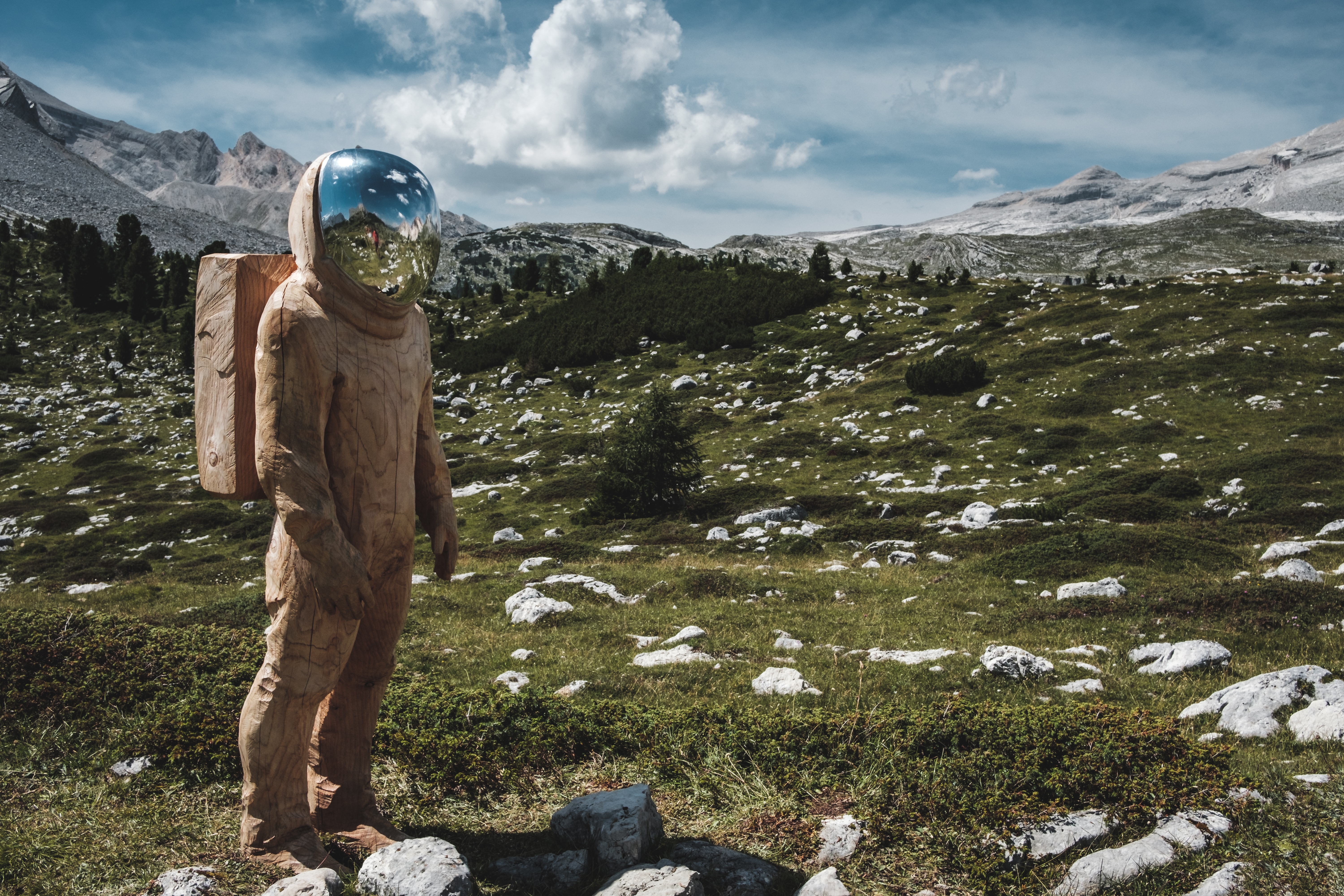 An astronaut looking person in a hazmat suit backpacking in the mountains.
