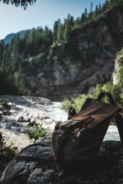 brown knapsack on top of gray rock