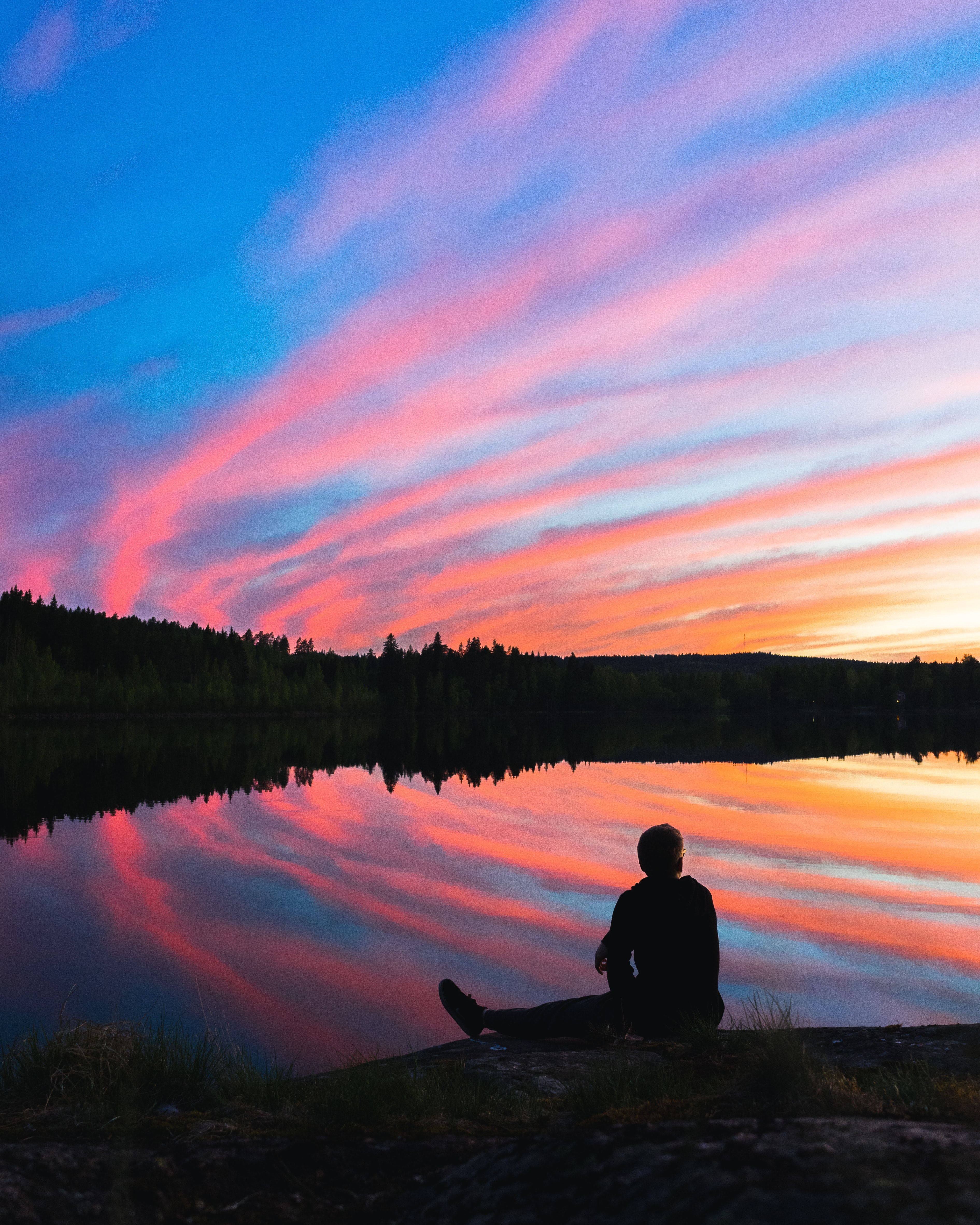 silhouette of man sitting on water's edge facing mountain during golden hour