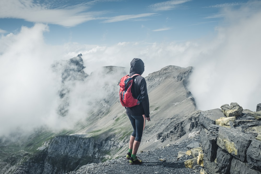 man wearing black hooded jacket and backpack standing on rocks facing clouds