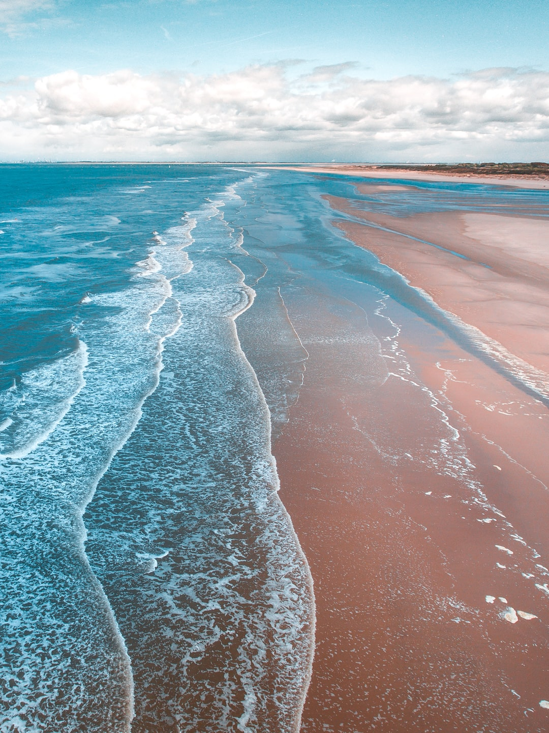 Crystal blue waves coming in onto a sandy beach.