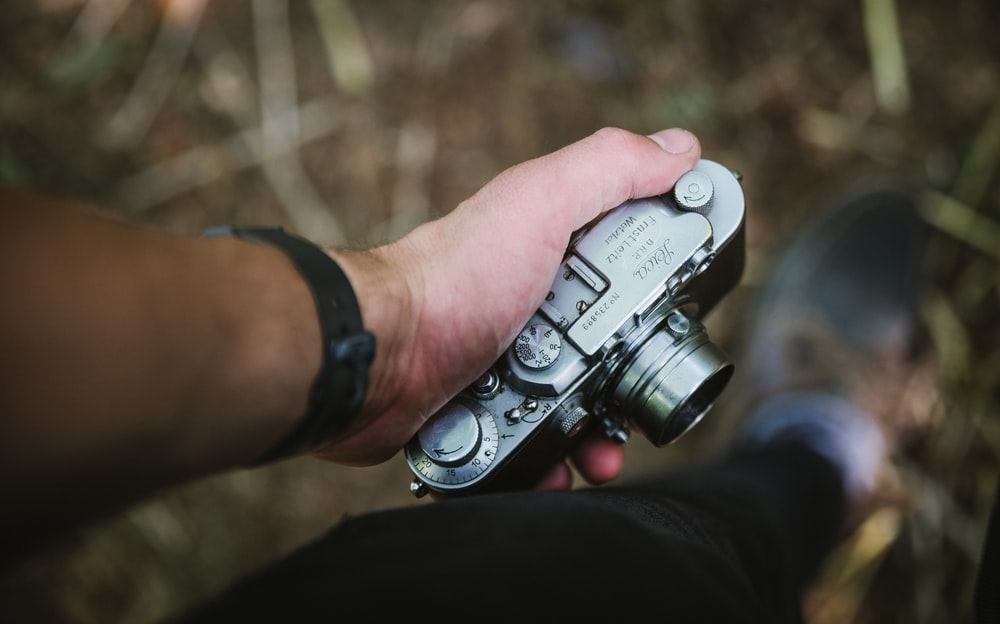 person holding silver point-and-shoot camera