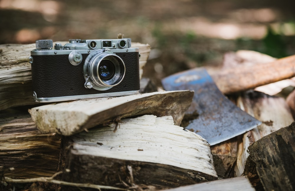 black and gray camera beside axe