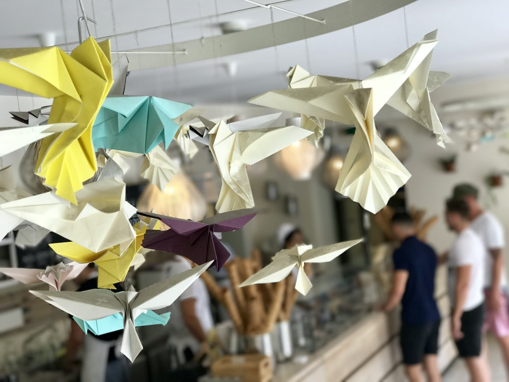 white, yellow, and teal paper bird decorations