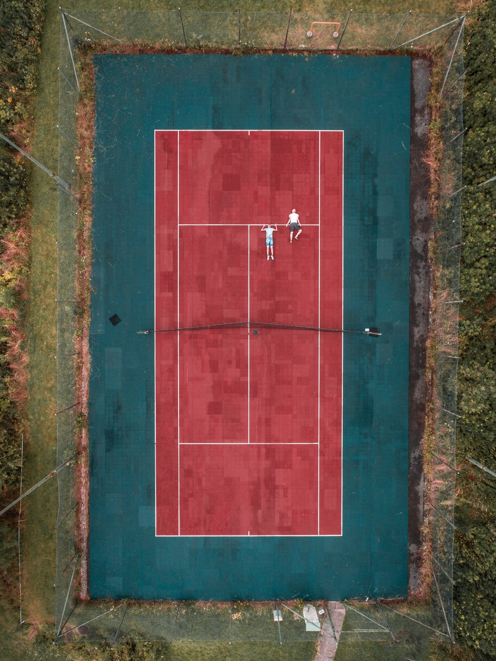 two person lying on tennis court
