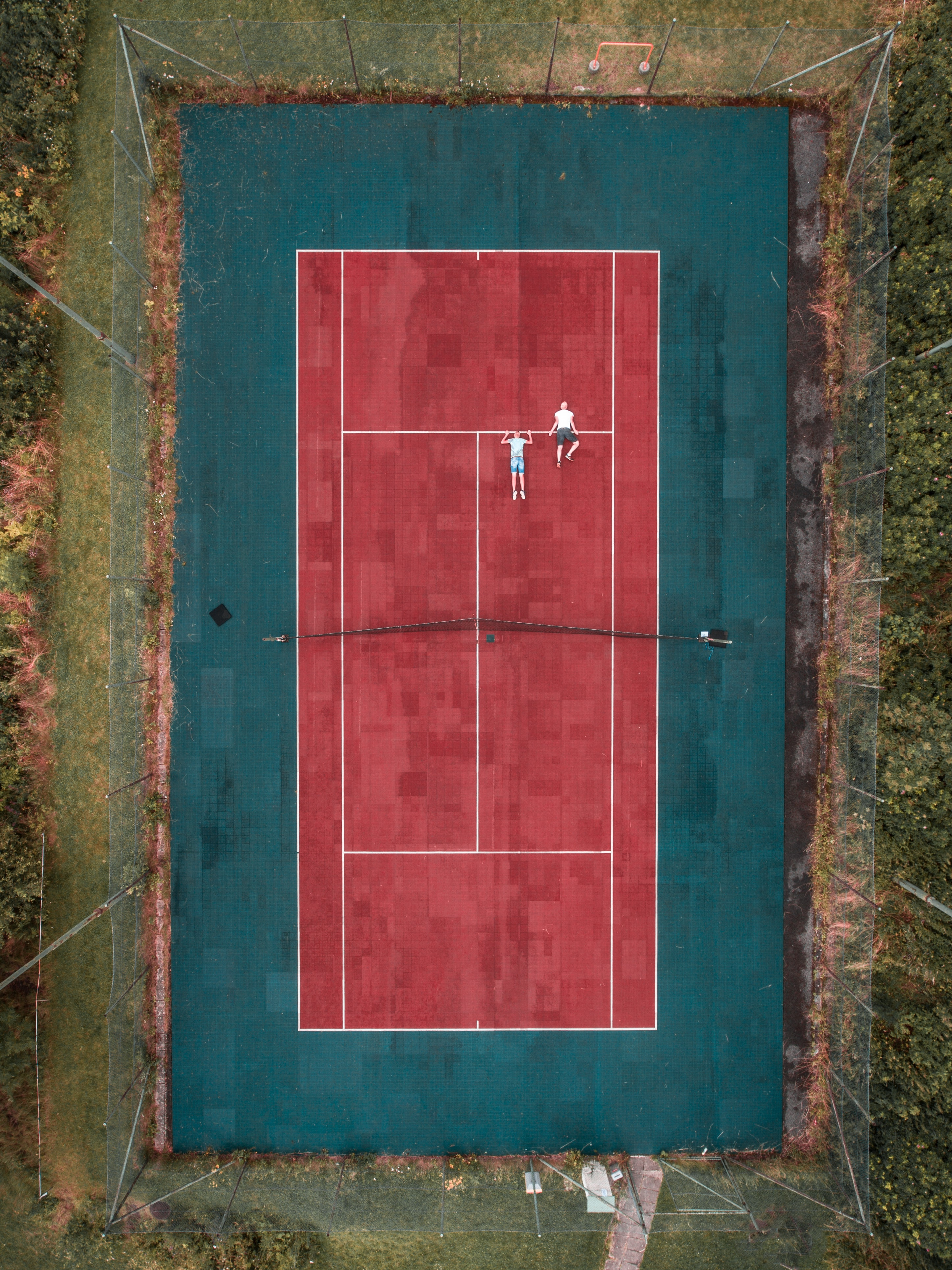 A drone looking down at an outdoor tennis court.