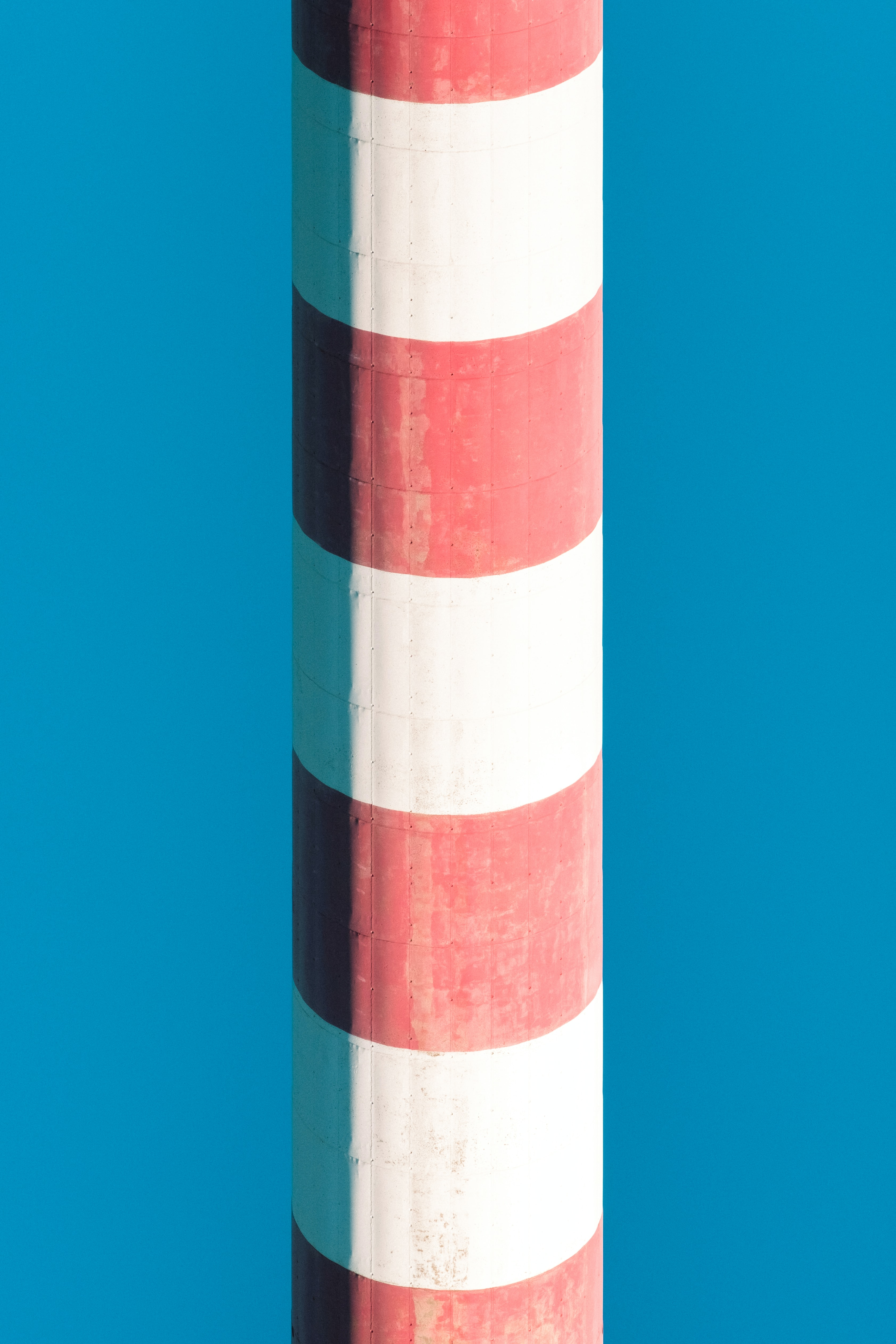 white and red striped pillar on blue background