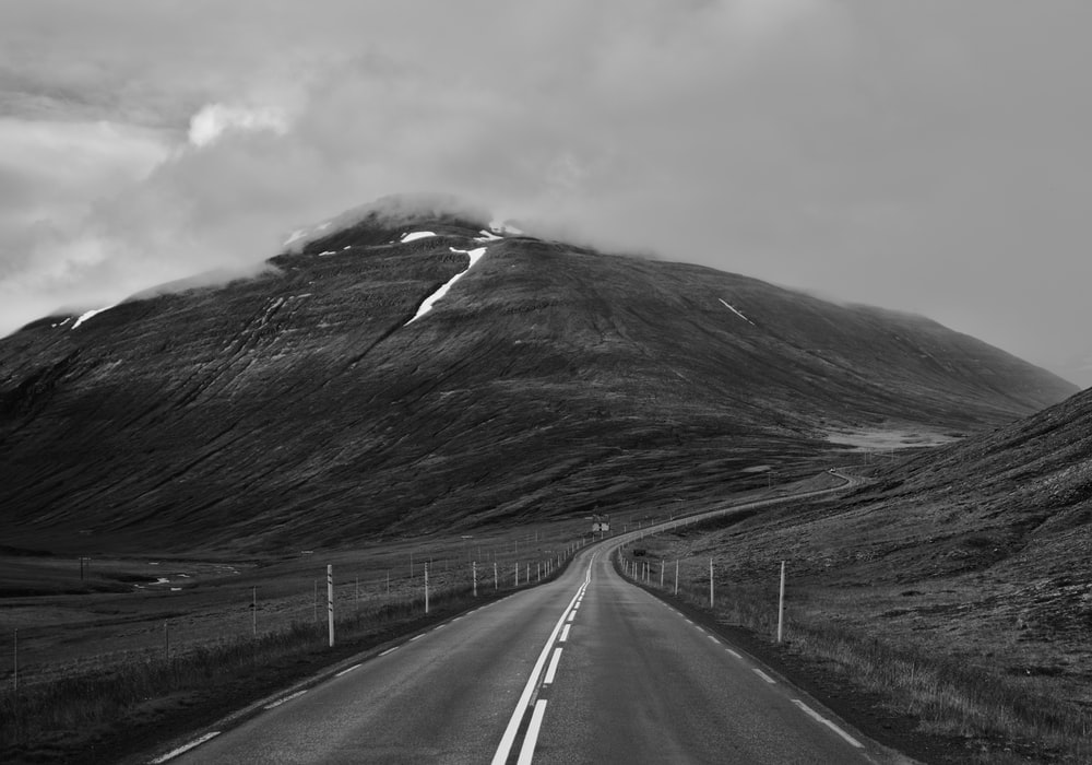 grayscale photo of road and mountain