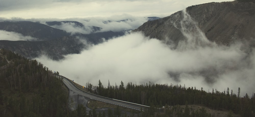 aerial photo of road and mountains with white fogs at daytime