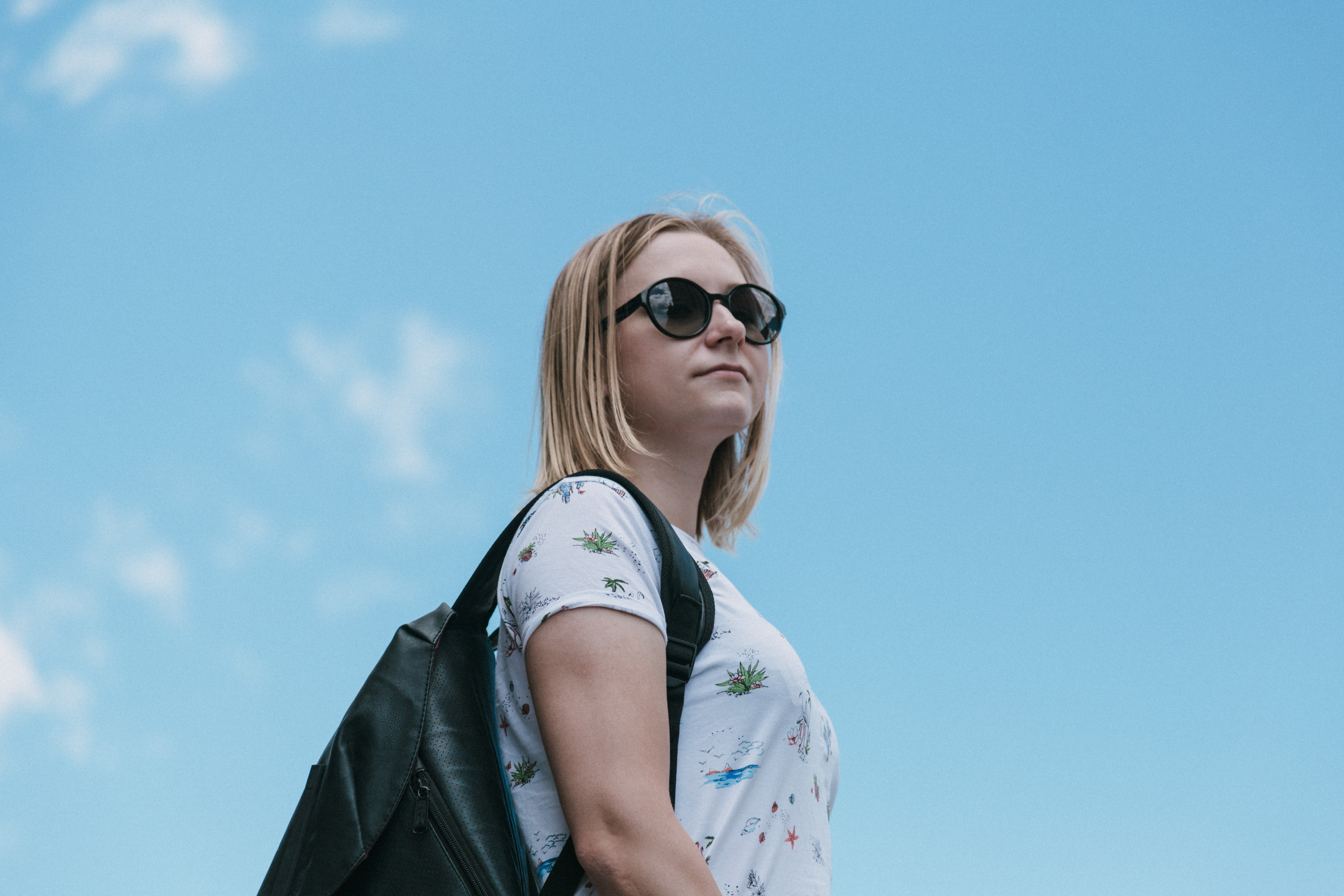 Student wearing a backpack and sunglasses against a blue sky