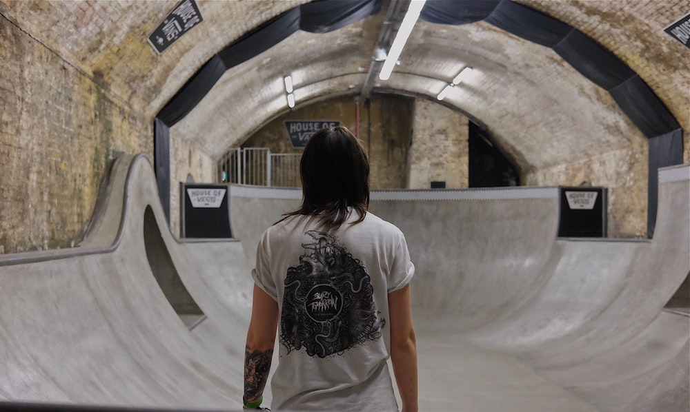 person wearing white top inside tunnel