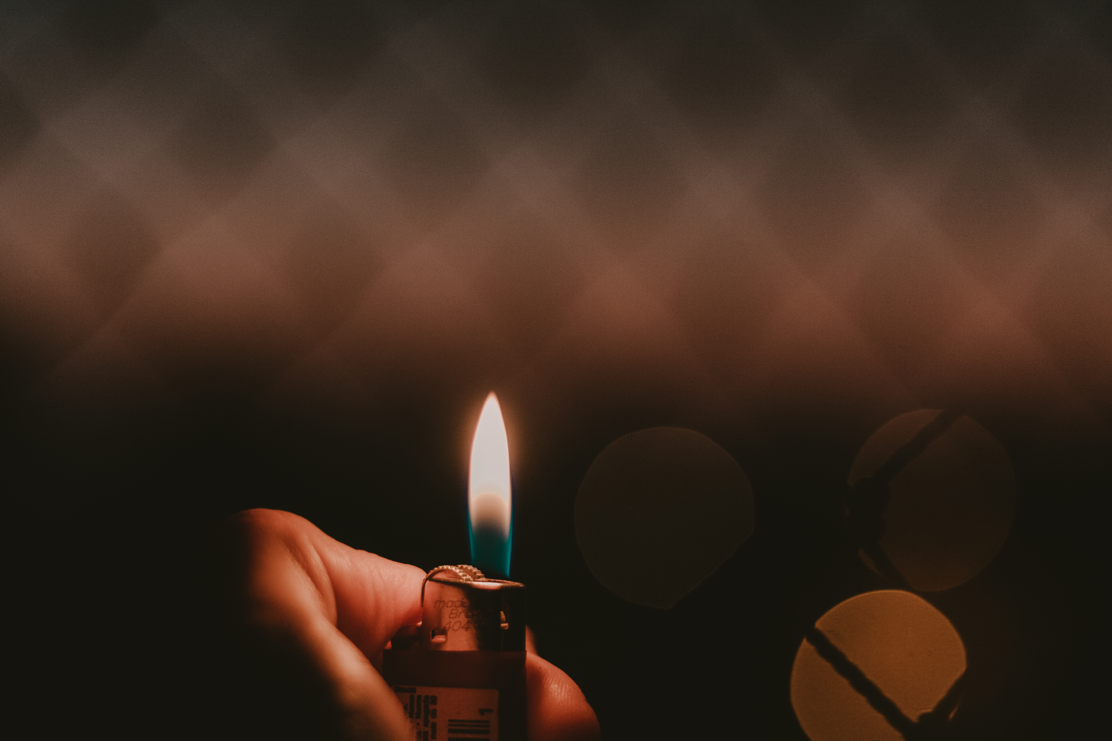 Hand holds a lighter with a blue and yellow flame in the dark how to pick the best dabs