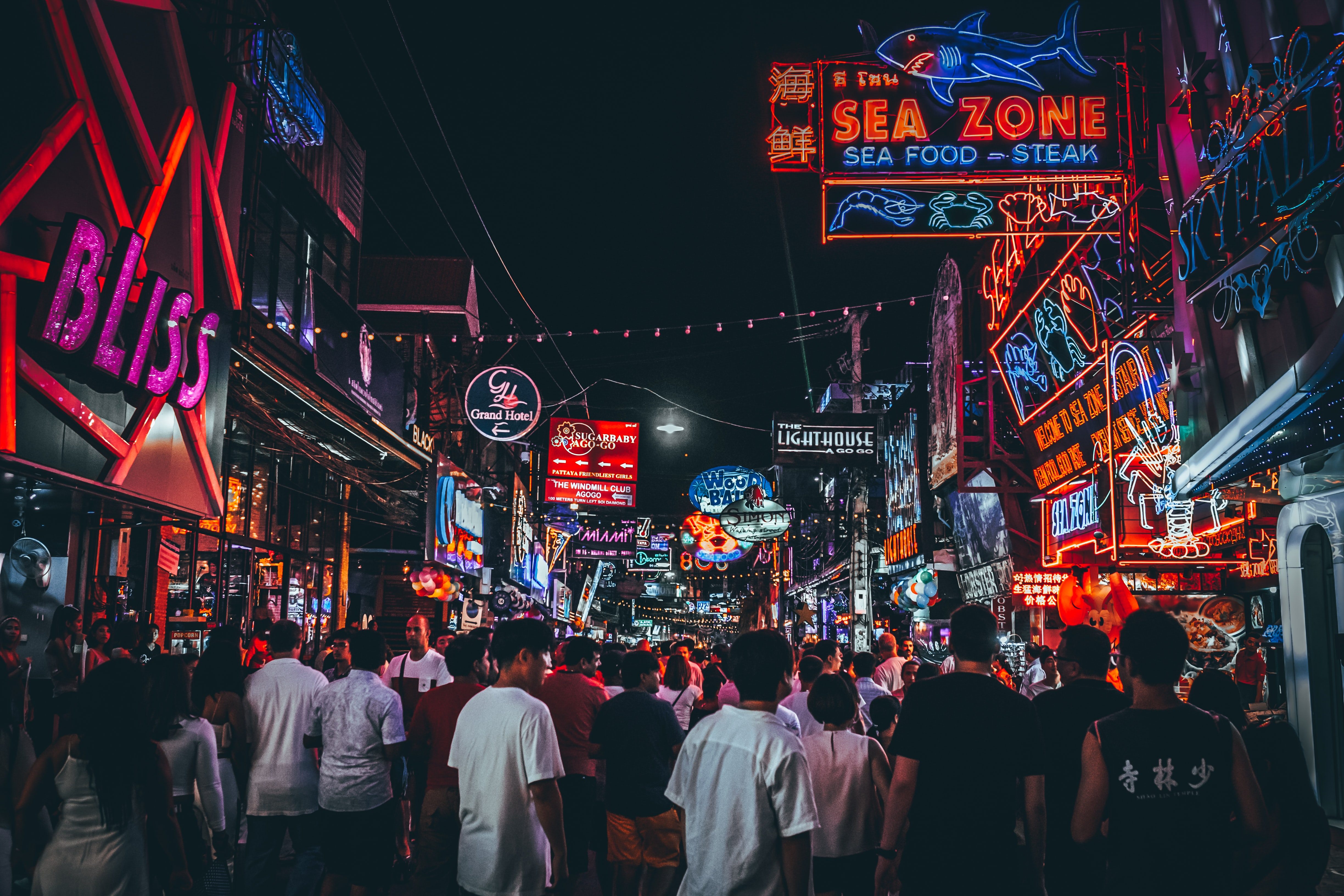 A street full of small shops and restaurants with bright LED signs.