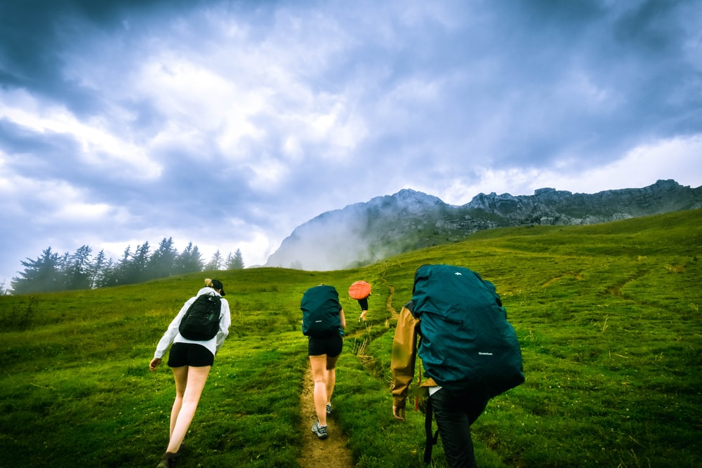 four person hiking on mountain hill during daytime