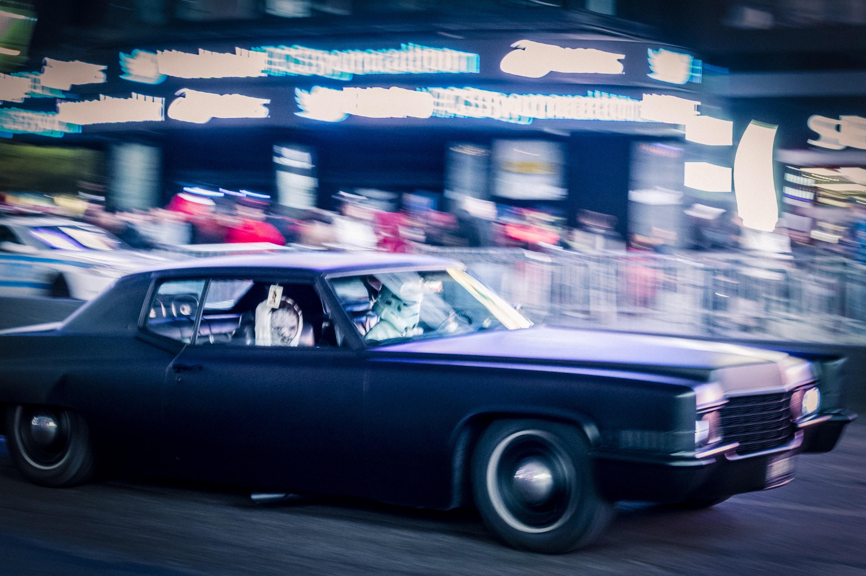 panning photo of purple car on road
