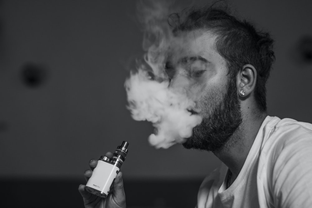 grayscale photo of man vaping