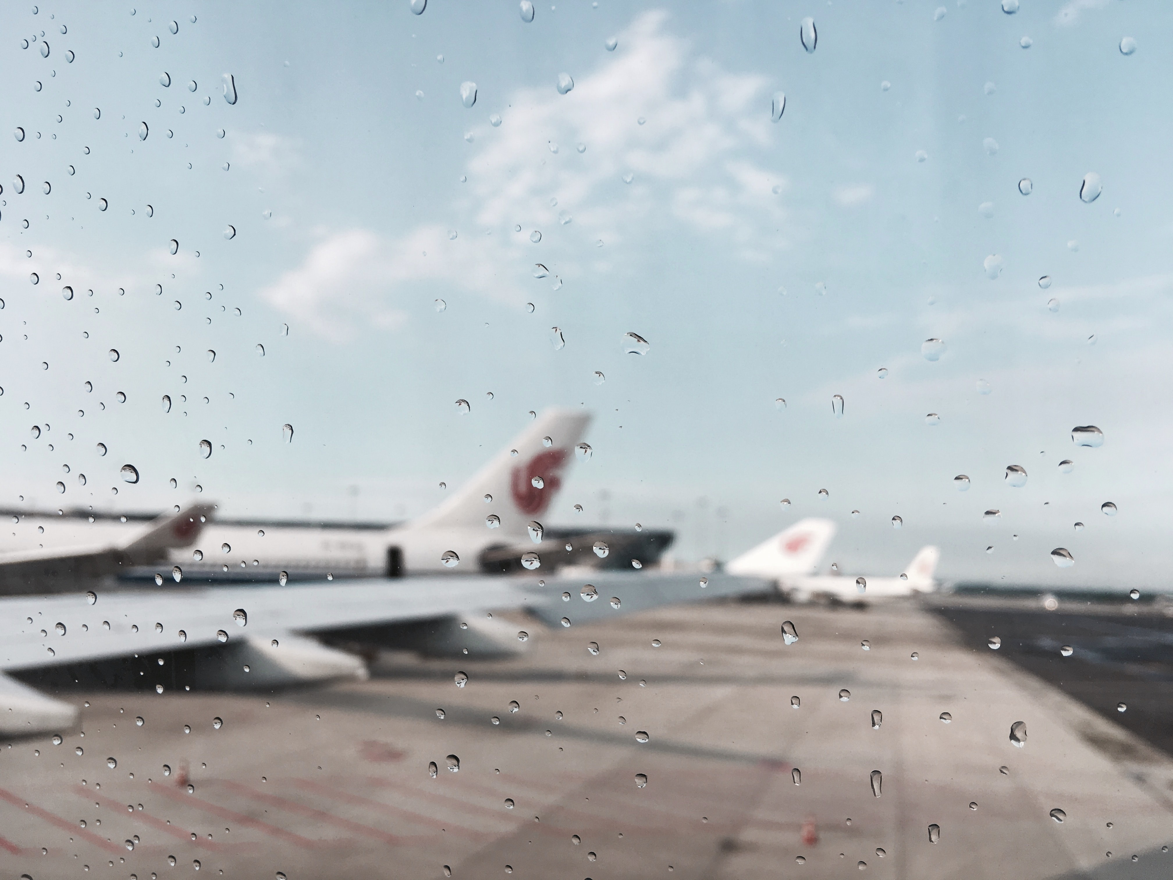 Planes at an airport, taken with a rain covered camera.