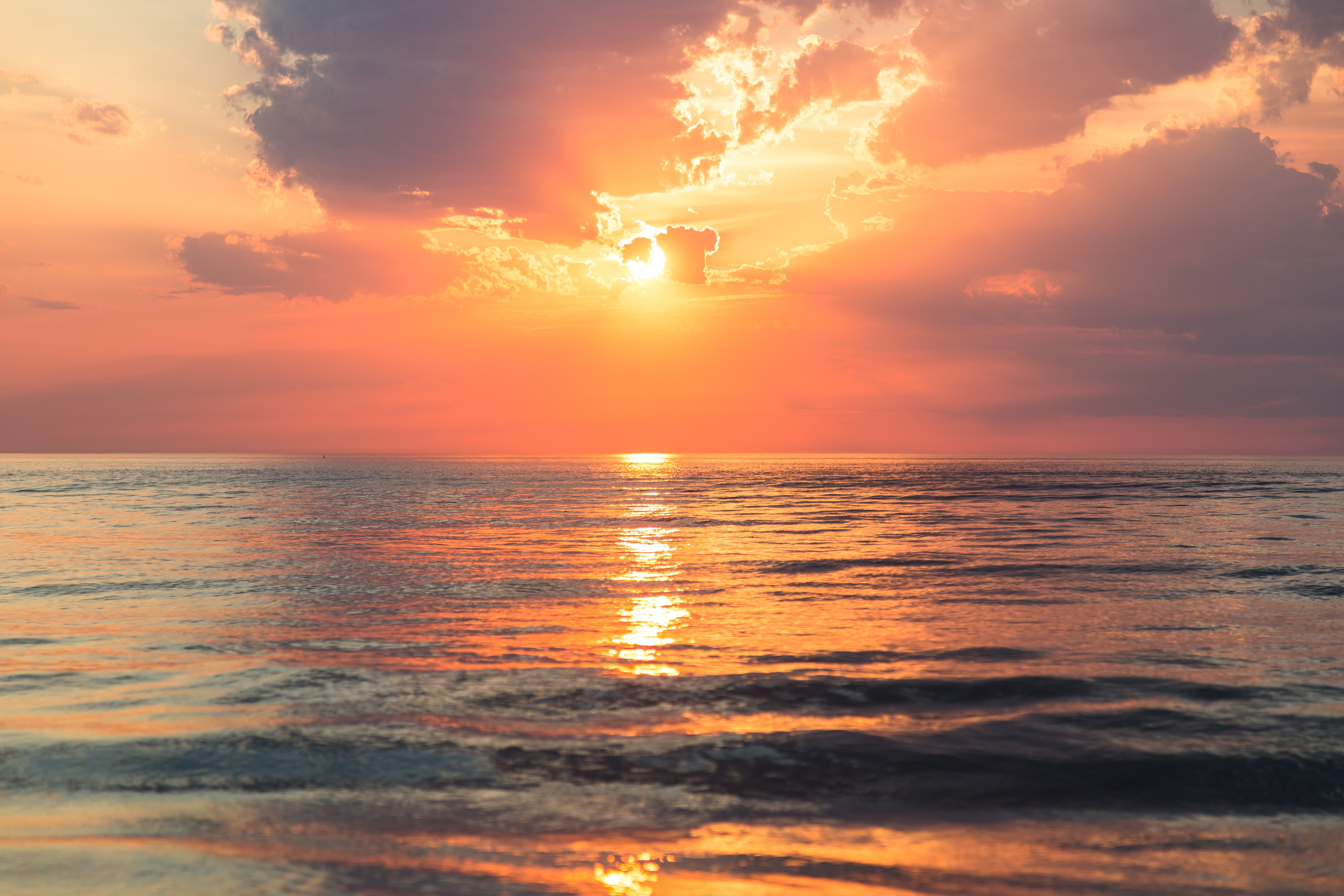 A beautiful sunset in a cloudy sky, casted above a calm ocean.