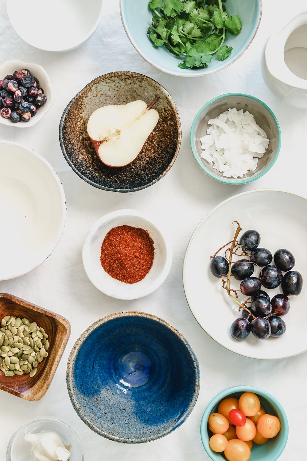 An overhead shot of fruits, seeds and spices in bowls