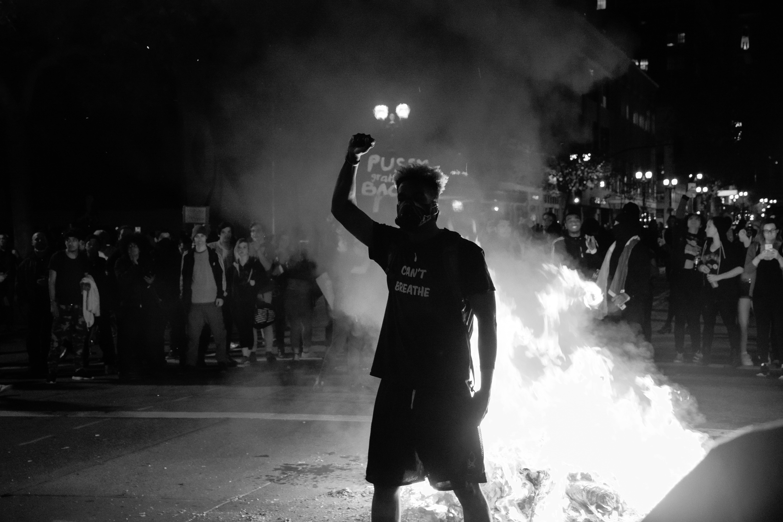 man raising his right hand near bonfire