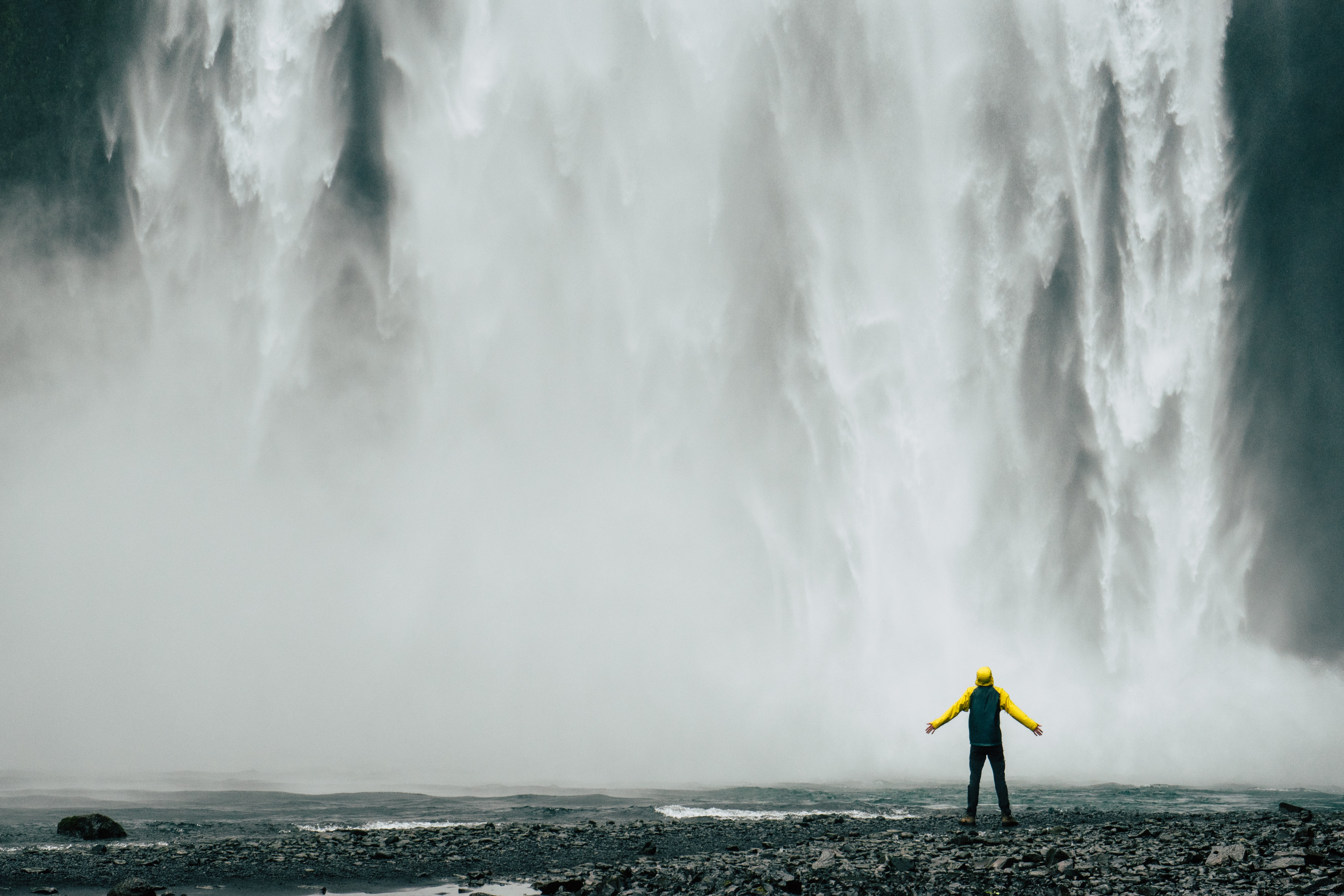 man standing in front of waterfalls at daytime