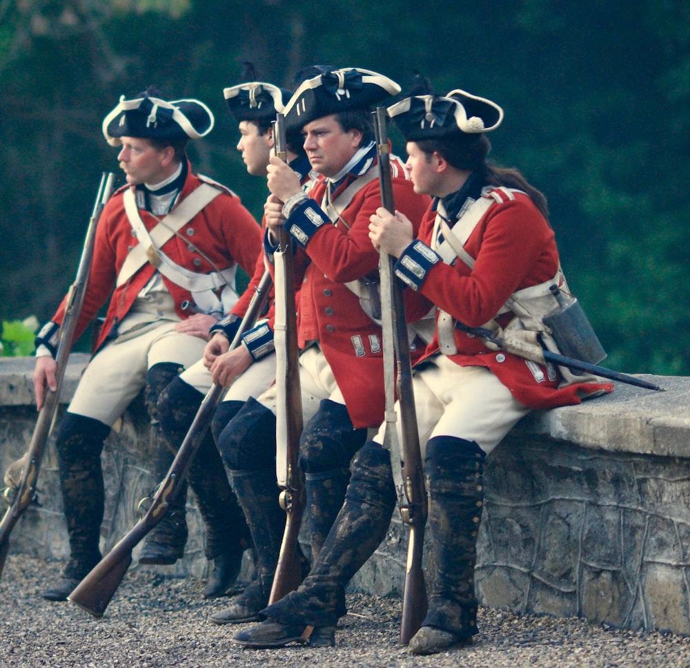 four men in uniforms holding rifles