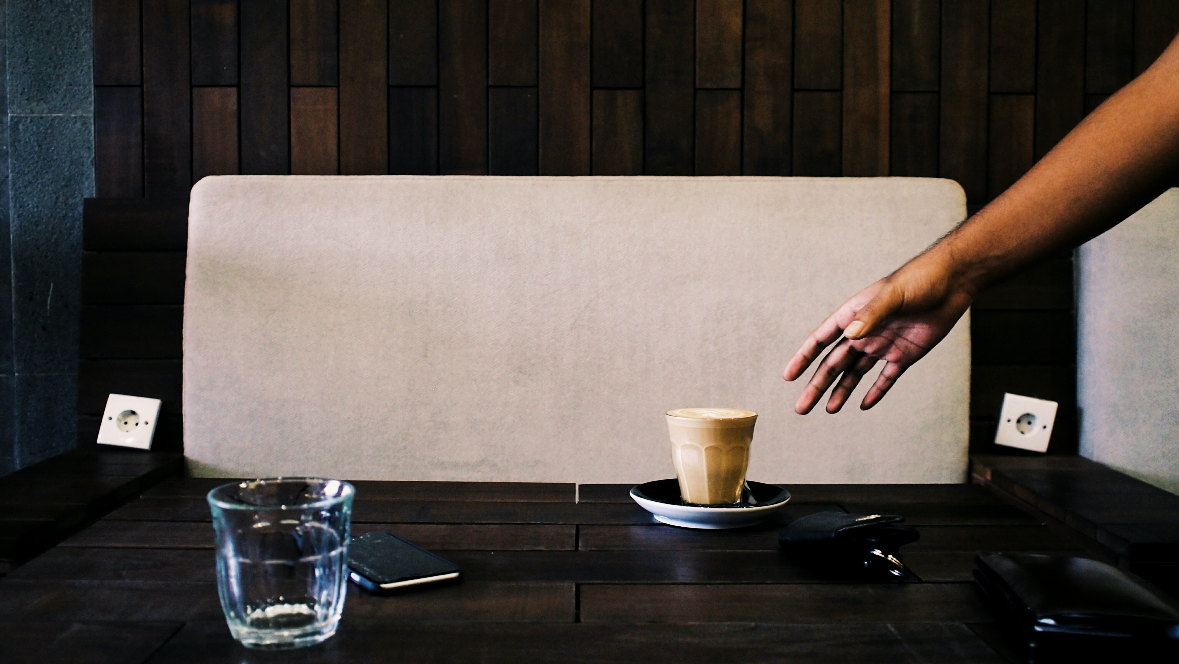 Person reaching for coffee mug on modern, wood table
