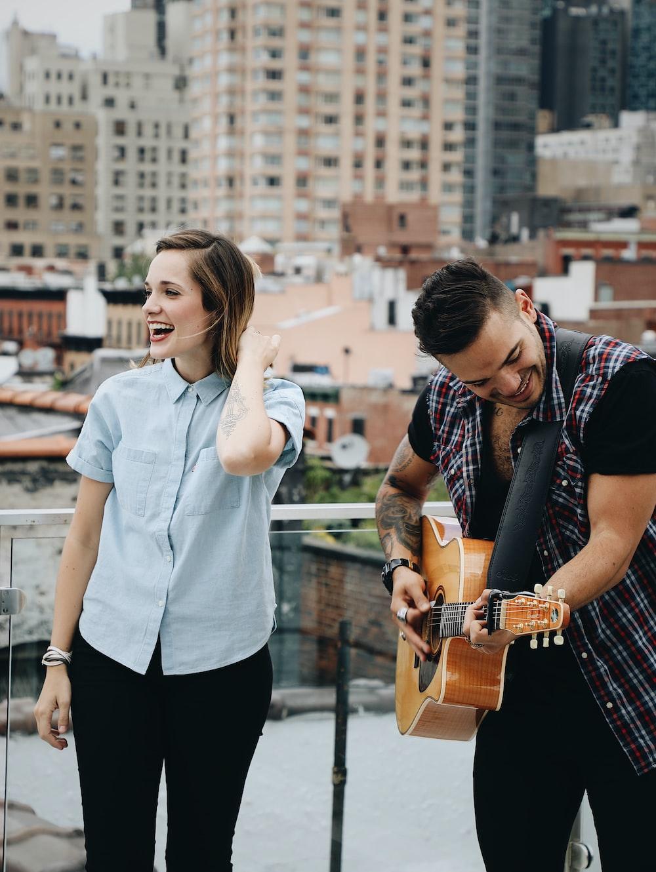 man playing guitar beside singing woman