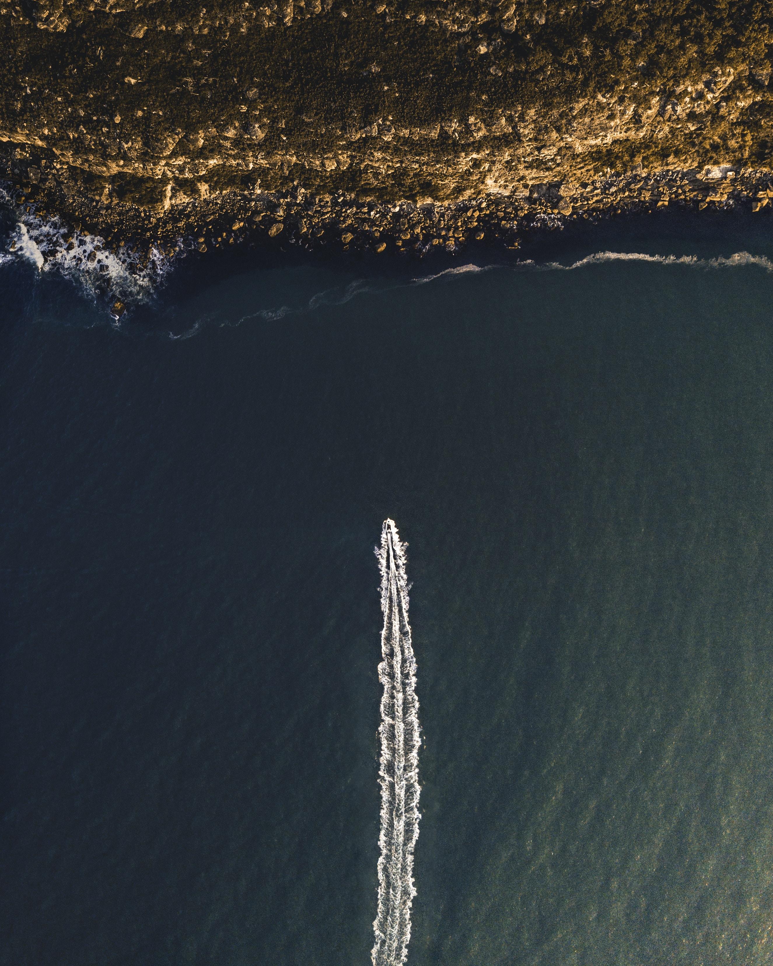 bird's eye view photography of speedboat towards coastline