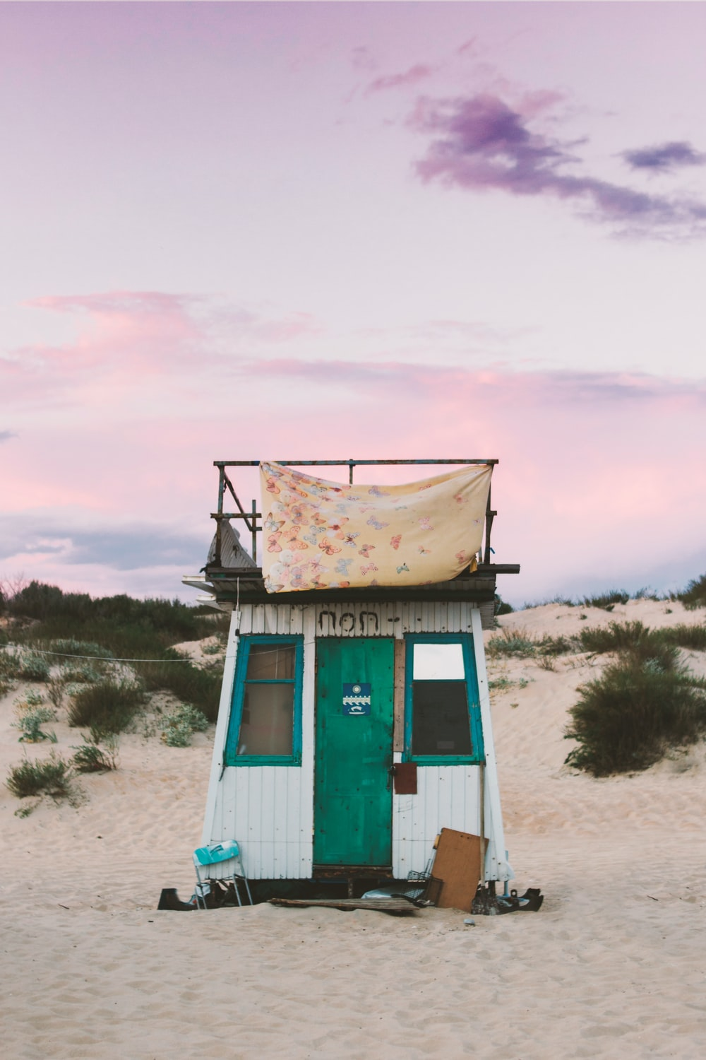 white and green shed on sand