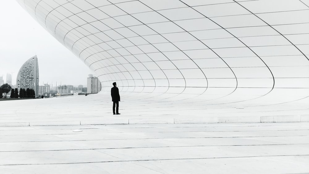 person standing in a middle of white plate field