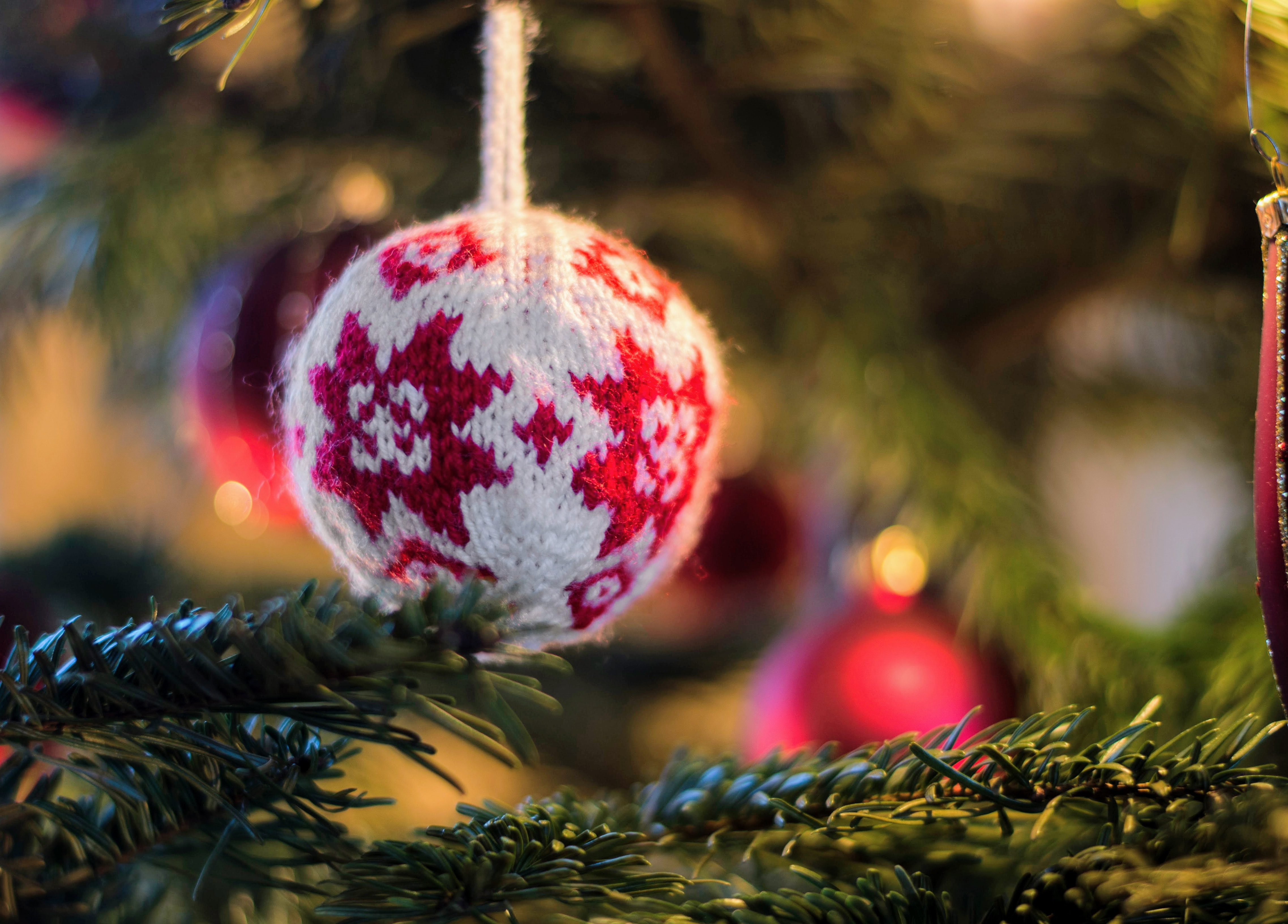 white and red knit bauble on green Christmas tree