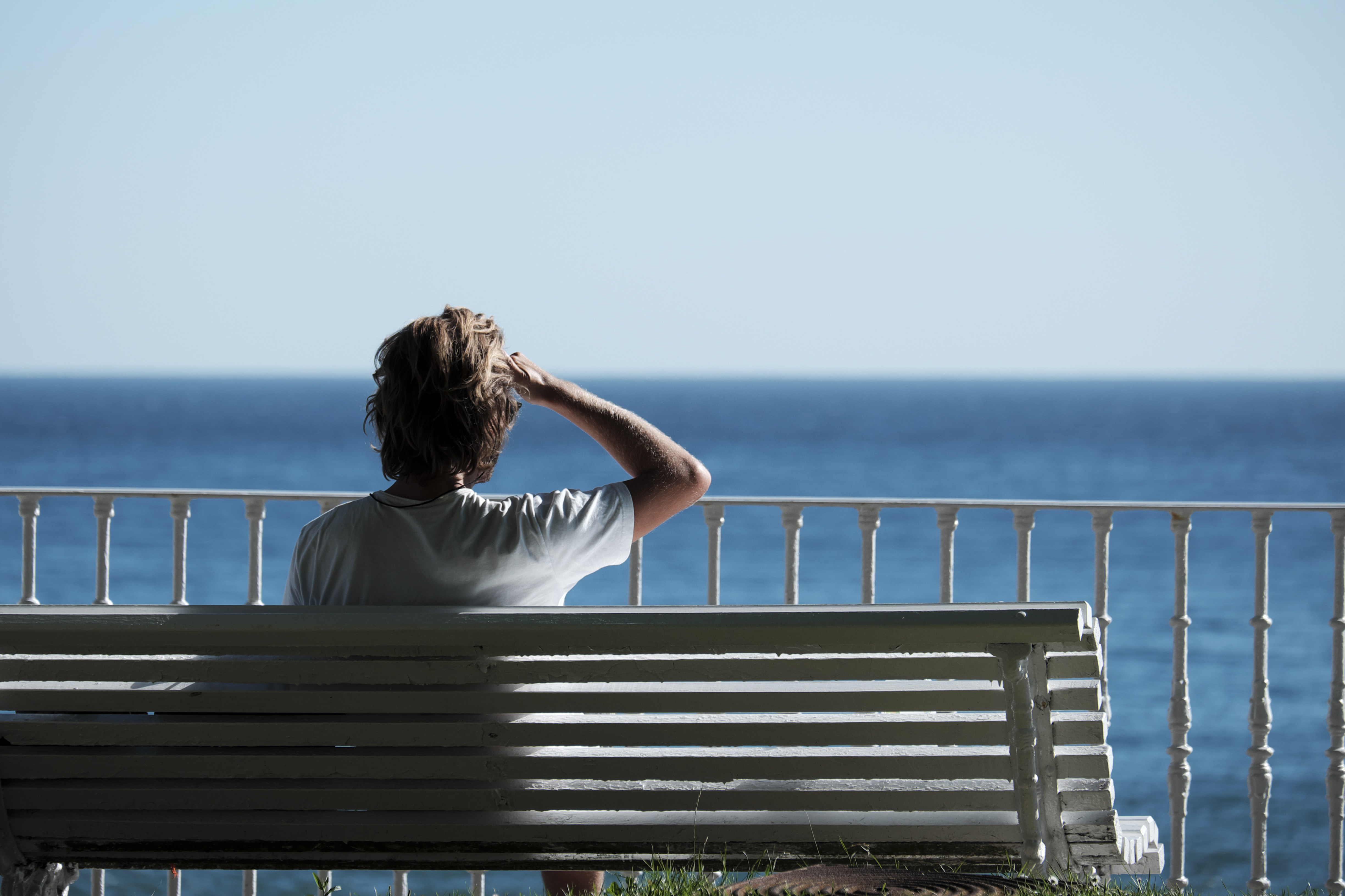 man sitting on bench near body of water during daytime